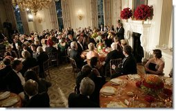 President George W. Bush addresses guests during the official dinner for India's Prime Minister Dr. Manmohan Singh, in the State Dining Room, Monday evening, July 18, 2005, at the White House.  White House photo by Eric Draper