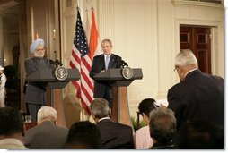 President George W. Bush and India's Prime Minister Dr. Manmohan Singh, listen to a reporter's question during a joint news conference, Monday, July 18, 2005, in the East Room of the White House.  White House photo by Eric Draper