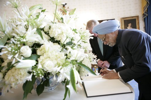India's Prime Minister Dr. Manmohan Singh is accompanied by U.S. Department of State Chief of Protocal Ambassador Donald Ensenat, Monday, July 18, 2005, as Singh signs the guest book upon his arrival to the White House. White House photo by Eric Draper
