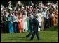 President George W. Bush and India's Prime Minister Dr. Manmohan Singh are cheered by invited guests, Monday, July 18, 2005 on the South Lawn of the White House, during the official arrival ceremony for Prime Minister Singh. White House photo by Lynden Steele