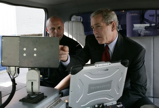 President George W. Bush talks with a Homeland Security officer, Wednesday, July 20, 2005, as President Bush is shown mobile security scanning equipment during a customs and border protection demonstration at the Port of Baltimore in Baltimore, Md. White House photo by Eric Draper