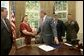 President George W. Bush shakes the hands of Janet and Bill Norwood after signing into law H.R. 1001, the Naming of the Sergeant Byron W. Norwood Post Office Building, designating the US Postal Service facility in Pflugerville, Texas, in honor of their 25-year-old son who died in combat in Iraq. Joining the Norwoods and the President for the signing are Congressman Michael McCaul, R-Texas, and First Lt. T.Ryan Sparks, 3rd Battalion, 1st Marines. White House photo by Eric Draper