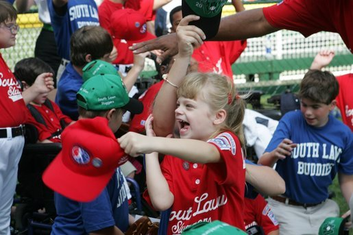 A young ballplayer from the West University Little League Challengers from Houston, Texas, cheers with her team Sunday, July 24, 2005, at a Tee Ball game on the South Lawn of the White House. White House photo by Carolyn Drake