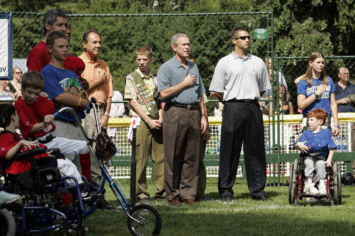 President George W. Bush listens to the National Anthem before a Tee Ball game on the South Lawn of the White House between the District 12 Little League Challengers from Williamsport, PA and the West University Little League Challengers from Houston, Texas on Sunday July 24, 2005. White House photo by Paul Morse