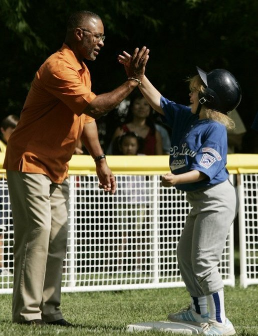 A player from the District 12 Little League Challengers of Williamsport, Pa., is given a high-five from baseball star and Tee Ball third base coach Ozzie Smith, Sunday, July 24, 2005, during a Tee Ball game on the South Lawn of the White House. White House photo by Paul Morse