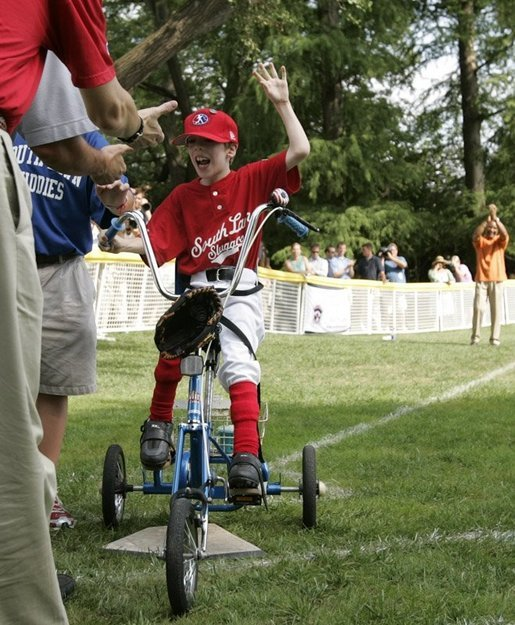 A player from the West University Little League Challengers from Houston, Texas, is welcomed as he crosses homeplate to score a run, Sunday, July 24, 2005, during a Tee Ball game on the South Lawn of the White House. White House photo by Paul Morse
