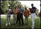 President George W. Bush laughs with Major League Baseball Hall of Fame players Ozzie Smith and Paul Molitor and former umpire Steve Palermo while congratulating Challenger Tee Ball players after a game on the South Lawn of the White House on Sunday July 24, 2005. White House photo by Paul Morse