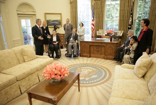 President George W. Bush gives a tour of the Oval Office after the signing of the Presidential Proclamation to Commemorate the 15th Anniversary of the Americans with Disabilities Act in the Oval Office Tuesday, July 26, 2005. President George H. W. Bush is pictured at center, left. White House photo by Eric Draper