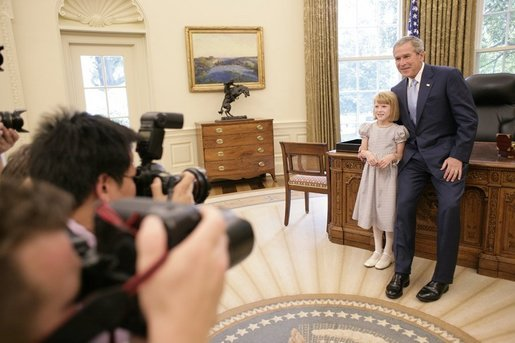 President George W. Bush and Navy Anderson, the 2005 March of Dimes National Ambassador, meet in the Oval Office, Wednesday, July 27, 2005 and pose for photographers. Navy Anderson, 7, and her family are in Washington to attend the March of Dimes National Youth Conference. White House photo by Eric Draper