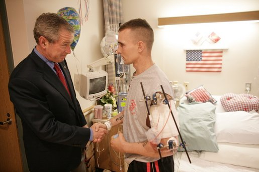 President George W. Bush shakes the hand of Marine Cpl. Anthony Gower after presenting him with a Purple Heart Saturday, July 30, 2005, at the National Naval Medical Center in Bethesda, Md. The Pittsburgh, Pa. native is recovering from injuries received in Operation Iraqi Freedom. White House photo by Eric Draper