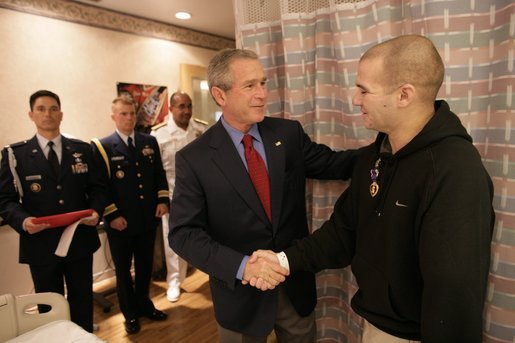 President George W. Bush shakes the hand of Cpl. Sean Locker after presenting the Marine with the Purple Heart Saturday, July 30, 2005, at the National Naval Medical Center in Bethesda, Md. Cpl. Locker, from Jessup, Md., is recovering from injuries suffered while serving in Operation Iraqi Freedom. White House photo by Eric Draper