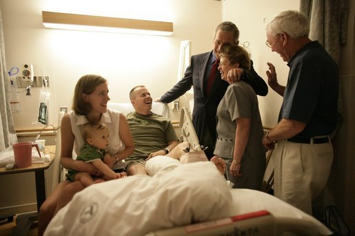 "President George W. Bush hugs Molly Sloan, mother of Capt. Stephen ""Kyle"" Sloan, during a visit with the Marine and his family Saturday, July 30, 2005, at the National Naval Medical Center in Bethesda, Md. Other members of the family include Capt. Sloan's wife, Courtney, 10-month-old son Samuel, and father, Carlos. Capt. Sloan is recuperating from injuries suffered during Operation Iraqi Freedom. White House photo by Eric Draper"