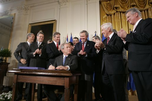 President George W. Bush acknowledges the applause of legislators and administration officials Tuesday, Aug. 2. 2005 in the East room of the White House, as he signs the CAFTA Implementation Act. White House photo by Paul Morse