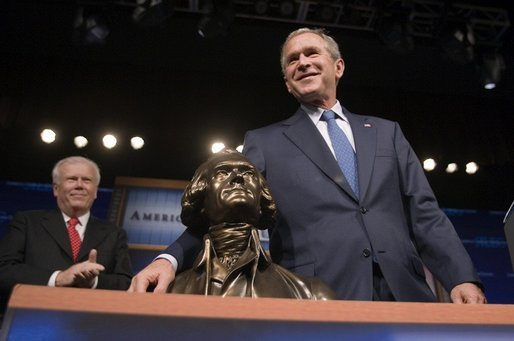 President George W. Bush poses with the American Legislative Exchange Council's Thomas Jefferson Freedom Award after speaking to the group in Dallas, Texas on Wednesday August 3, 2005. White House photo by Paul Morse