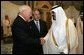 Former President George H. W. Bush, left, shake hands with newly crowned King Abdullah, right, during a retreat at King Abdullah's Farm in Riyadh, Saudi Arabia Friday, August 5, 2005, following the death of his half-brother King Fahd who passed away August 1, 2005. Interperter Gamal Helal, center, is also pictured. White House photo by David Bohrer