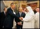 Former President George H. W. Bush, left, shake hands with newly crowned King Abdullah, right, during a retreat at King Abdullah's Farm in Riyadh, Saudi Arabia Friday, August 5, 2005, following the death of his half-brother King Fahd who passed away August 1, 2005. Interpreter Gamal Helal, center, is also pictured. White House photo by David Bohrer