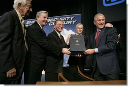 President George W. Bush holds the box containing the energy bill after signing the H.R. 6, The Energy Policy Act of 2005 at Sandia National Laboratory in Albuquerque, New Mexico, Monday, Aug. 8, 2005. Also on stage from left are Congressman Ralph Hall (R, TX), Congressman Joe Barton (R, TX), Senator Pete Domenici (R, NM) and Senator Jeff Bingaman (D, NM).  White House photo by Eric Draper