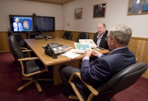 President George W. Bush is handed a map by Deputy Chief of Staff Joe Hagin, center, during a video teleconference with federal and state emergency management organizations on Hurricane Katrina from his Crawford, Texas ranch on Sunday August 28, 2005. White House photo by Paul Morse