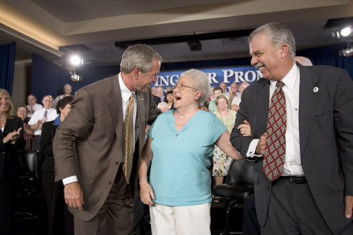 President George W. Bush and Margaret Cantrell break out in laughter on stage Monday, Aug. 29, 2005, at the Pueblo El Mirage RV Resort and Country Club in El Mirage, Arizona. The 82-year-old retired Scottsdale grandmother was on hand to lend support to the President's Conversation on Medicare. White House photo by Paul Morse