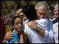 President George W. Bush comforts Bronwynne Bassier, right, and her sister Kim after landing in Biloxi, Miss., Friday Sept. 2, 2005, as part of his tour of the Hurricane Katrina-ravaged Gulf Coast. Their family lost everything in the wake of the devastating storm. White House photo by Eric Draper