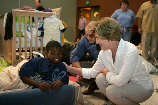 Laura Bush visits with a young boy displaced by Hurricane Katrina in the Cajundome at the University of Louisiana in Lafayette, La., Friday, Sept. 2, 2005. White House photo by Krisanne Johnson