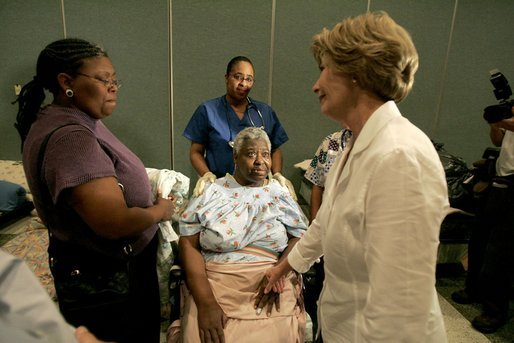 "Laura Bush reaches out to a victim of Hurricane Katrina during a visit Friday, Sept. 2, 2005, to the Cajundome at the University of Louisiana in Lafayette. ""The people of this part of the United States, the Lafayette area of Louisiana, are very, very warm people,"" said Mrs. Bush. ""They've opened their hearts, and many of them have opened their homes, as well, to people from New Orleans -- family members and strangers."" White House photo by Krisanne Johnson"