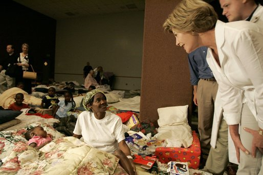 Laura Bush leans down to comfort a woman and her young child inside the Cajundome at the University of Louisiana in Lafayette, Friday, Sept. 2, 2005, during her visit to the center, one of many created to accommodate victims of Hurricane Katrina. White House photo by Krisanne Johnson