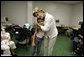 "First Lady Laura Bush hugs a young girl displaced by Hurricane Katrina during her visit Friday, Sept. 2, 2005, to the Cajundome at the University of Louisiana in Lafayette. ""Some things are working very, very well in Louisiana,"" Mrs. Bush said. ""And certainly this center is one of those."" White House photo by Krisanne Johnson"