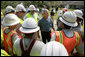 President George W. Bush talks with some workers of Alabama Power, who are helping to bring power back in service in Poplarville, Miss., Monday, Sept. 5, 2005. White House photo by Eric Draper