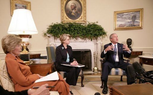 "President George W. Bush, seen with U.S. Secretary of Education Margaret Spellings, center, and Laura Bush, left, gestures as he speaks with reporters, Tuesday, Sept. 6, 2005 in the Oval Office at the White House, about efforts the Department of Education is undertaking with a program, ""Hurricane Help for Schools,"" established to assist schools and students affected by Hurricane Katrina. White House photo by Eric Draper"
