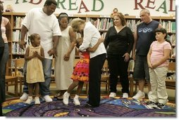 Laura Bush embraces a child Thursday, Sept. 8, 2005 of one of the families from New Orleans, displaced last week as a result of Hurricane Katrina, during a meeting at the Greenbrook Elementary School in DeSoto County, Miss. Greenbrook Elementary School has enrolled the most displaced students among the DeSoto County schools in Mississippi.  White House photo by Krisanne Johnson