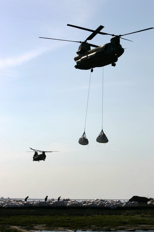Helicopters lift sandbags that will be dropped into the area of the levee break to facilitate repairs to 17th street levee in New Orleans, Louisiana Thursday, September 8, 2005. White House photo by David Bohrer