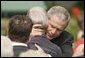 President George W. Bush embraces one of the hundreds of family and friends who gathered on the South Lawn of the White House, Friday, Sept. 9, 2005, during the 9/11 Heroes Medal of Valor Award Ceremony, in honor of the courage and commitment of emergency services personnel who died on Sept. 11, 2001. White House photo by Paul Morse