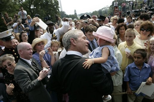 President George W. Bush holds Keira Corrigan of Mineola, N.Y., as he meets some of the hundreds of family and friends who gathered on the South Lawn of the White House, Friday, Sept. 9, 2005, during the 9/11 Heroes Medal of Valor Award Ceremony, in honor of the courage and commitment of emergency services personnel who died on Sept. 11, 2001. White House photo by Eric Draper
