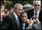 President George W. Bush poses for a photo with a young man wearing a button in honor of 9/11 victim, Yamel J. Merino, as he met some of the hundreds of families and friends who gathered on the South Lawn of the White House, Friday, Sept. 9, 2005, during the 9/11 Heroes Medal of Valor Award Ceremony, in honor of the courage and commitment of emergency services personnel who died on Sept. 11, 2001. White House photo by Eric Draper