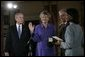 President George W. Bush watches as Karen Hughes is sworn-in by U.S. Secretary of State Condoleezza Rice, Friday, Sept. 9, 2005 at the State Department in Washington, to be the Under Secretary of State for Public Diplomacy. Jerry Hughes, Secretary Hughes' husband, holds the Bible during the ceremony. White House photo by Eric Draper