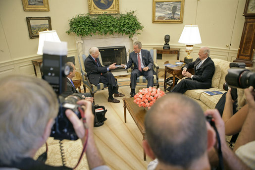 President George W. Bush accepts a report from former President Jimmy Carter and Secretary of State James Baker, Co-Chairs of the Carter-Baker Commission on Federal Election Reform, in the Oval Office Monday, Sept. 19, 2005. White House photo by Eric Draper