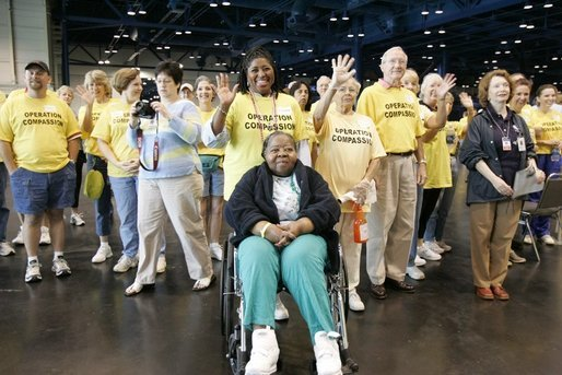 """Operation Compassion"" volunteers wave to First Lady Laura Bush Monday, Sept. 19, 2005, as she visited Houston's George R. Brown Convention Center. The Convention Center was designated a shelter for Hurricane Katrina evacuees and since opening its doors Sept. 2, more than 35,000 have been served and approximately 46,000 volunteers have been trained. White House photo by Krisanne Johnson"