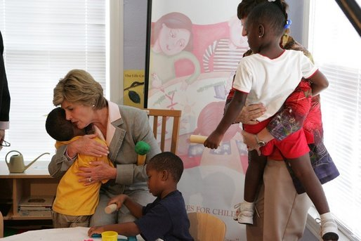 Mrs. Laura Bush receives a hug from a young boy at the House of Tiny Treasures in Houston during her visit Monday, Sept. 19, 2005. The House enables parents to search for jobs and housing, and to run errands while their children receive good care from credentialed teachers. White House photo by Krisanne Johnson