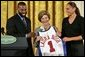 Golden State Warrior Baron Davis, left, and Phoenix Mercury guard Diana Taurasi, right, present Laura Bush with a basketball jersey at the National Book Festival Author's breakfast in the East Room Saturday, Sept. 24, 2005. White House photo by Krisanne Johnson