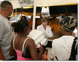 Laura Bush helps give out meals to families, while visiting a medical and food distribution site, Tuesday, Sept. 27, 2005 in Biloxi, Miss.  White House photo by Krisanne Johnson