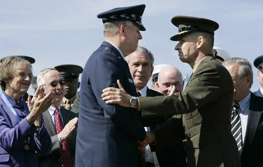 General Richard B. Myers, left, and General Peter Pace shake hands Friday, Sept. 30, 2005, during The Armed Forces Farewell Tribute in Honor of General Myers and the Armed Forces Hail in Honor of General Pace at Fort Myer's Summerall Field in Ft. Myer, Va., with Mary Jo Myers and President George W. Bush looking on. White House photo by Paul Morse