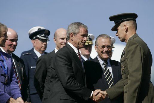 President George W. Bush congratulates U.S. Marine General Peter Pace, after Pace was sworn-in Friday, Sept. 30, 2005, as the new Chairman of the Joint Chiefs of Staff, at the Armed Forces Farewell Tribute in Honor of General Richard B. Myers and Armed Forces Hail in Honor of General Pace at Fort Myer in Ft. Myer, Va. Defense Secretary Donald Rumsfeld is seen center. White House photo by Shealah Craighead