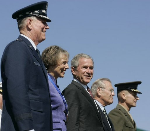 General Richard B. Myers, Mary Jo Myers, President George W. Bush, Secretary of Defense Donald Rumsfeld, and General Peter Pace, observe the March in Review, the Joint Service Medley and the Flyover during the Chairman of the Joint Chiefs of Staff change of command, Friday, Sept. 30, 2005, at The Armed Forces Farewell Tribute in Honor of General Richard B. Myers and Armed Forces Hail in Honor of General Peter Pace at Fort Myer's Summerall Field in Ft. Myer, Va. White House photo by Shealah Craighead