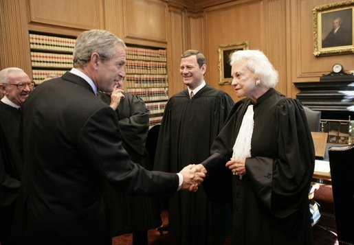 President George W. Bush shakes hands with U.S. Supreme Court Associate Justice Sandra Day O' Connor, during his visit to the U.S. Supreme Court for the investiture ceremony for U.S. Chief Justice John Roberts, seen background-center, Monday, Oct. 3, 2005 in Washington. Associate Justice John Paul Stevens is seen at left. White House photo by Eric Draper