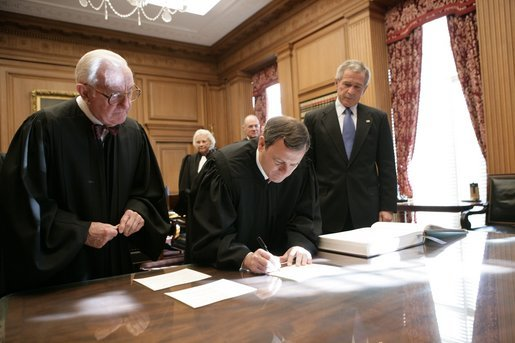 President George W. Bush looks on as U.S. Supreme Court Chief Justice John Roberts signs documents during his investiture ceremony at the U.S. Supreme Court, Monday, Oct. 3, 2005 in Washington. Associate Justice John Paul Stevens is seen at left, and Associate Justices Sandra Day O'Connor and Anthony Kennedy, background. White House photo by Eric Draper