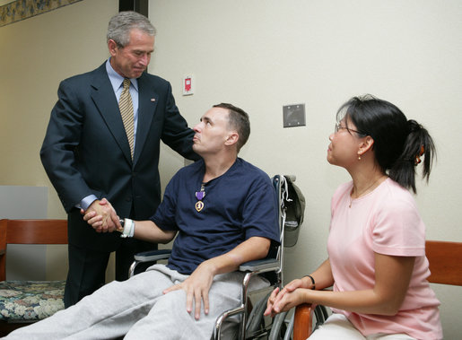 President George W. Bush shakes the hand of SFC Richard Robertson, of Knoxville, Tenn., Wednesday, Oct. 5, 2005, as his wife, Sarah Robertson, looks on. President Bush presented the Purple Heart to the soldier during his visit to Walter Reed Army Medical Center in Washington D.C. White House photo by Paul Morse