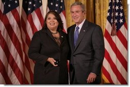 President George W. Bush stands with Volunteer Service Award recipient Marie Arcos of Houston, Texas, in the East Room of the White House, Friday, Oct. 7, 2005, where President Bush honored six recipients of the President's Volunteer Service Awards, as part of the celebration of Hispanic Heritage Month.  White House photo by Eric Draper