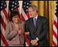 President George W. Bush stands with Volunteer Service Award recipient Maria Hines of Albuquerque, N.M., in the East Room of the White House, Friday, Oct. 7, 2005, where President Bush honored six recipients of the President's Volunteer Service Awards, as part of the celebration of Hispanic Heritage Month. White House photo by Eric Draper