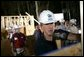 President George W. Bush dons a hard hat as he joins volunteers at a Habitat for Humanity building site Tuesday, Oct. 11, 2005, in Covington, La. White House photo by Eric Draper